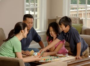 A family of four sitting around a table playing a board game.