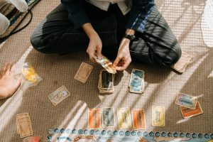 A top-down view of a board game player holding a handful of cards