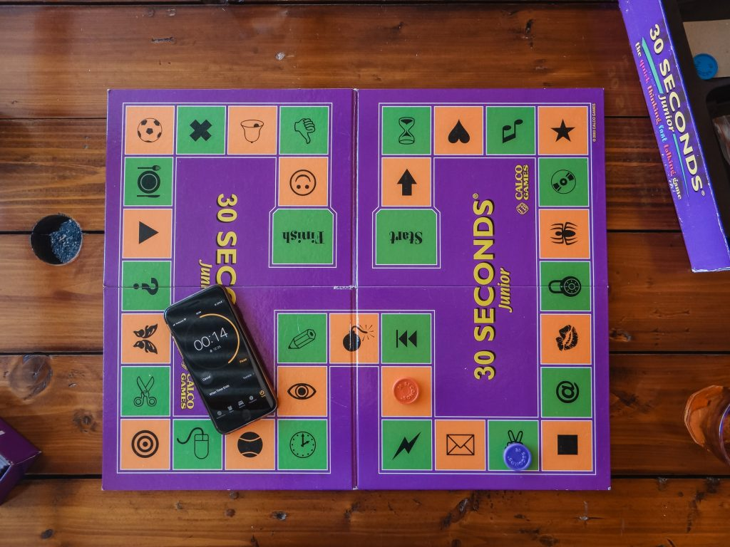 A top-down view of a board game on a table with a smartphone timer on the board.